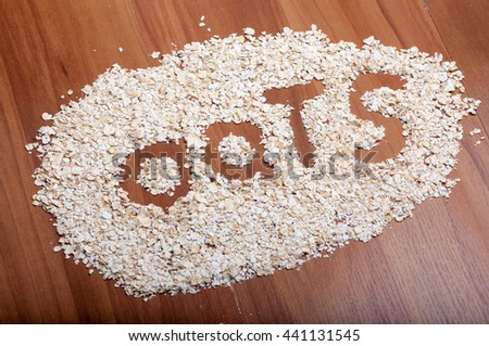 Oats word of oatmeal flakes on a wooden floor