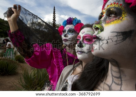 OAXACA, MEXICO, OCTOBER 30, 2015: Girls dressed as catrinas waiting for the carnival to start on the streets, during day of dead celebrations in Oaxaca  - stock photo