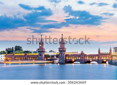 Oberbaum Bridge with subway and boat on the river Spree at night, Berlin - stock photo