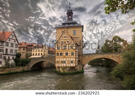 Obere bridge and Altes Rathaus and cloudy sky in Bamberg, Germany, sepia toned  - stock photo
