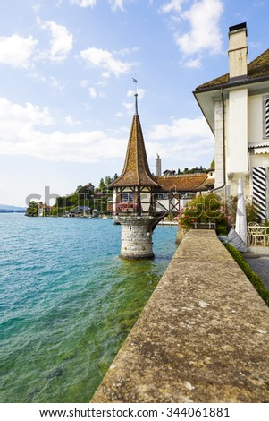 OBERHOFEN, SWITZERLAND - SEPTEMBER 08, 2015: Little tower in the lake Thun is a typical architectural addition of 19th-century to the Castle of Oberhofen which dates back history to the 13th century - stock photo