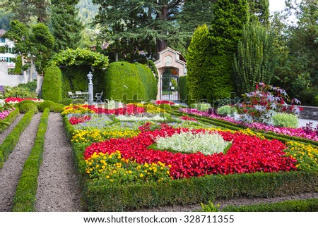 OBERHOFEN, SWITZERLAND - SEPTEMBER 08, 2015: The magnificent garden it is the pride of this wonderful romantic castle of Oberhofen which dates back history to the 13th century. - stock photo