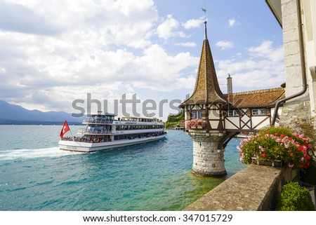 OBERHOFEN, SWITZERLAND - SEPTEMBER 08, 2015: The ship next to a small tower which is a typical architectural addition of 19th-century to the Castle of Oberhofen which dates back to the 13th century - stock photo