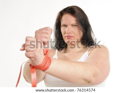 Obese adult woman her hands are tied with a measuring tape, she looks sadly in the camera, on white background