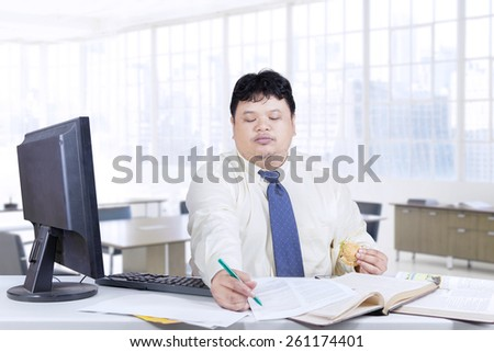 Obese entrepreneur working on the table while holding a burger, shot in the office - stock photo