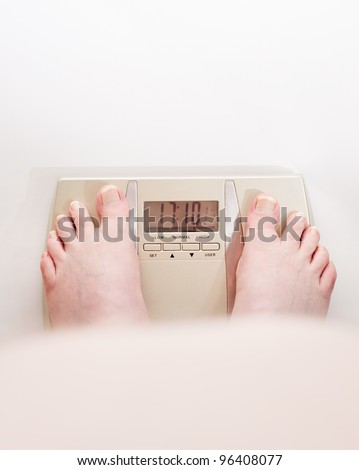 Obese man looking over his fat stomach at his feet on the weighing scales. - stock photo