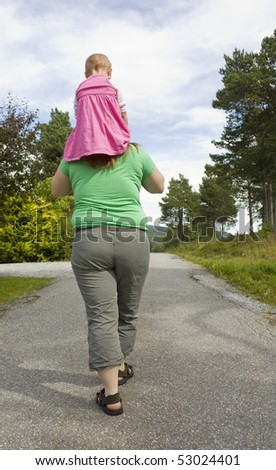 Obese mother carrying daughter on shoulders, exercising - stock photo