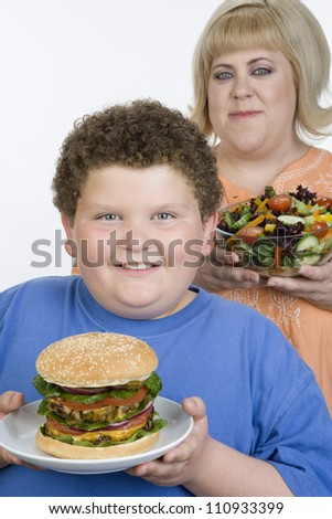 Obese teenage boy and mother with a bowl of salad and a hamburger - stock photo