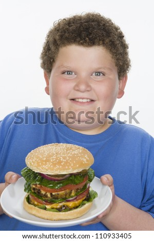 Obese teenage boy with a hamburger isolated over white background