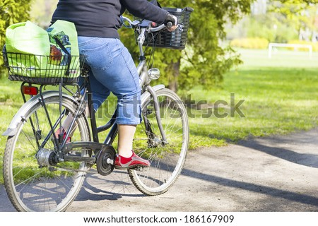 Obese woman riding a bike in spring park - stock photo