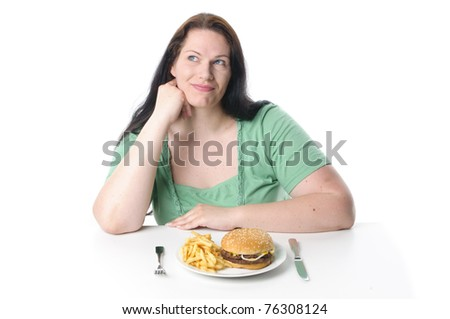 Obese woman with black hair sitting at the table and struggling with a hamburger and French fries, white background.