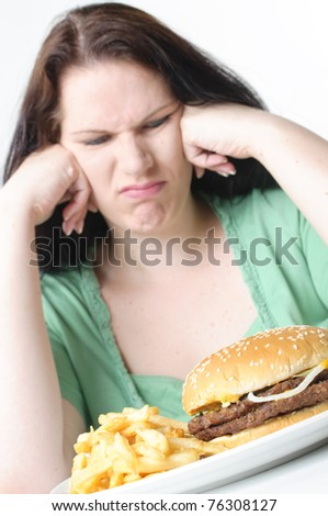 Obese woman with black hair sitting at the table and struggling with a hamburger and French fries, white background. - stock photo