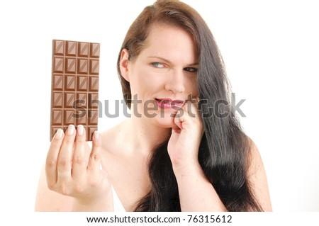 Obese woman with long black hair holding a chocolate bar in his hand and puts them to eat in front of white background. - stock photo