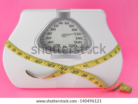 obesity concept with scale and measuring tape - stock photo