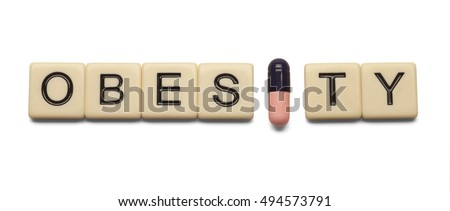 Obesity spelled out with lettered tiles and capsule on white background. Concept of health care. Clipping path included.