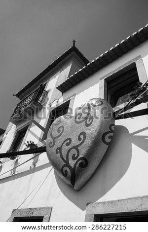 OBIDOS, PORTUGAL - APRIL 30, 2015: Typical house decorated with praline heart in golden wrap during the 13th  International Chocolate Festival in medieval town of Obidos.