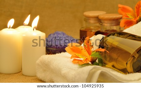 Object for the spa. Candles burning, pebble, a Lily, a bottle with oil, liquid soap, and more.