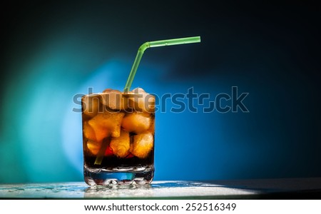 Object of glass transparent full glass with in form star ice cubes and Coke with a green and yellow tube on blue background Empty space for inscription  - stock photo