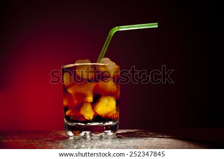 Object of transparent full glass with ice star cubes and sparkling carbonated diet coca coke cola with variety of green plastic tube on red dramatic background Empty Space for inscriptions - stock photo
