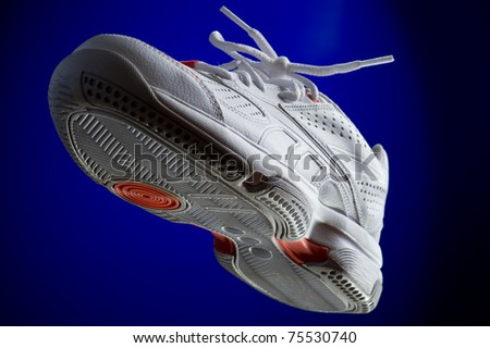 object on blue - white sneakers close up - stock photo