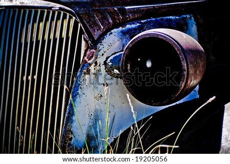 Objects in various stages of decay and aging, abandoned and forgotten - headlight and grille - stock photo