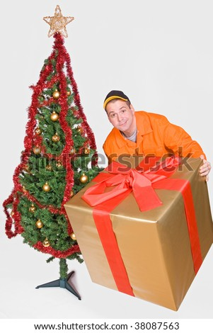 obliging supplier with Christmas box and Christmas tree - stock photo