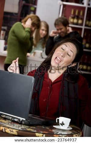 Obnoxious young woman singing loudly in a coffee house - stock photo