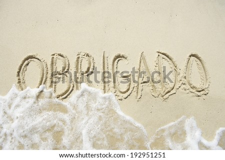 Obrigado thank you message in Portuguese handwriting in sand - stock photo