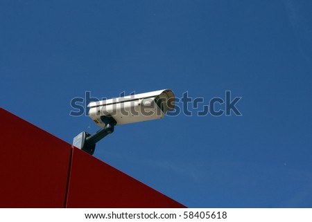 Observation camera on a red roof against the blue sky.