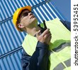 Observing docker in front of a stack of blue containers on a bright sunny day wearing sunglasses - stock photo