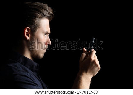 Obsessed angry teenager texting on the smart phone isolated on a black background                - stock photo