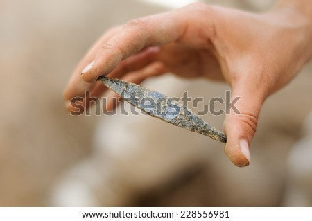 obsidian arrowhead isolated on archaeological background - stock photo