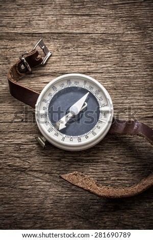 obsolete compass with leather strap on wooden table top in retro style - stock photo