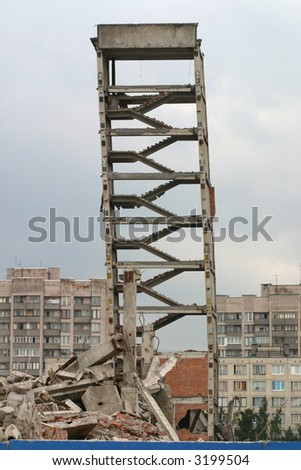 Obsolete gray building remain under deconstruction activity - stock photo