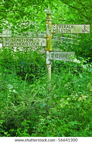 Obsolete signpost ravaged by nature at the side of a disused road in the Cornwall UK - stock photo