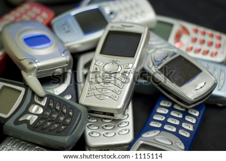 Obsolete technology. Unwanted mobile phones. - stock photo