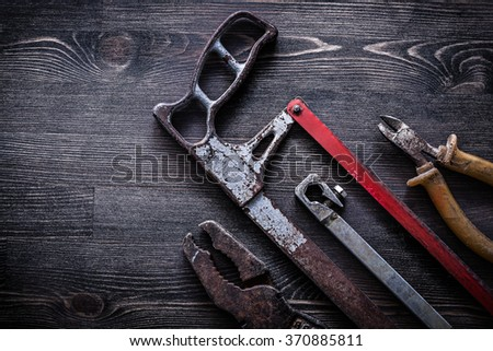 Obsolete vintage handsaw wire-cutter pliers on wooden board construction concept. - stock photo