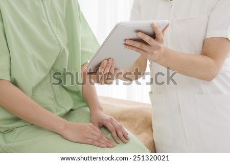 Obstetrician gynecologist with an electronic tablet - stock photo