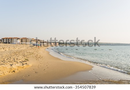 OBZOR, BULGARIA - AUG 15, 2015: The girl makes a morning jog along the beach. Colorful sunrise on the sea beach.  Picture taken in the morning during a trip to Bulgaria.