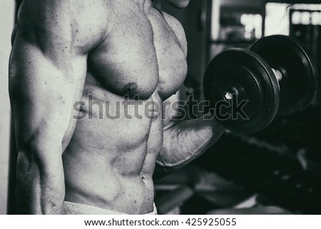 Occupation with dumbbells in the gym. Strong man with dumbbells