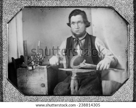 Occupational portrait of a blacksmith, working on a horseshoe at an anvil, other tools to his side. quarter plate daguerreotype, 1840-1860 - stock photo