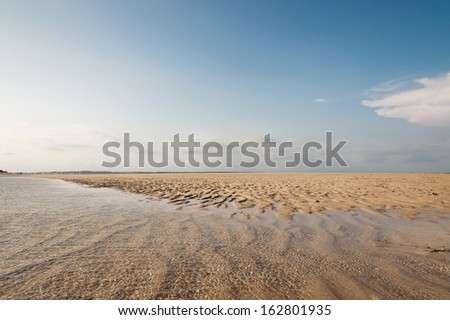 Ocean and beach with yellow sand and clear water at the sunset