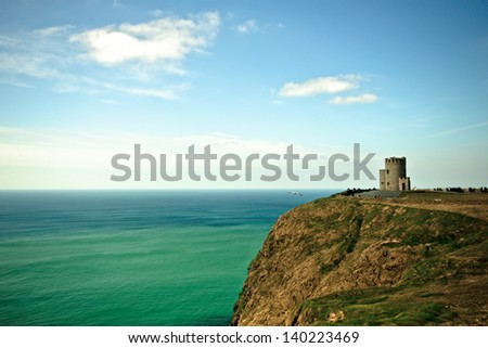 Ocean and O'Briens Tower on Cliffs of Moher in Ireland - stock photo