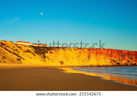 Ocean beach at sunset. Full moon in the sky. Sagres, Portugal - stock photo
