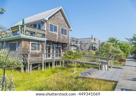 OCEAN BEACH, FIRE ISLAND, US, JULY 6, 2016: Typical house and wooden path - stock photo
