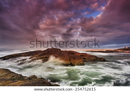 Ocean beach of rocks and sand at sunrise with stormy cloudy weather when first sun rays shed light on wet rocks - stock photo