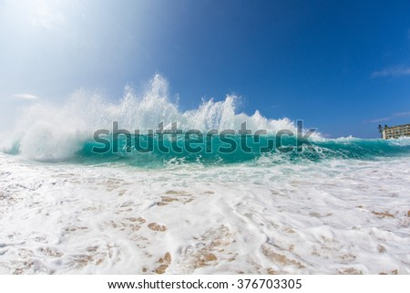 Ocean breaking surfing wave. Sea foam in bright sun light. Beautiful tropical oceanic background postcard. Big water splashes on seascapes. - stock photo