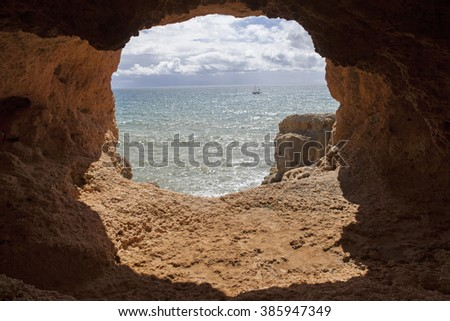 ocean cave and a boat in algarve, the south of portugal, Marinha beach