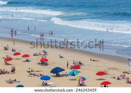 OCEAN CITY - JUNE 13: Tourists at the beach in Ocean City, MD on June 13, 2014. Ocean City, MD is a popular beach resort on the East Coast and it is one of the cleanest in the country. - stock photo