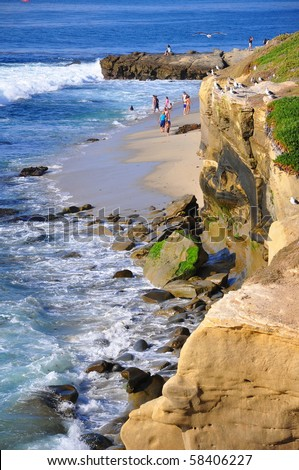 Ocean cliffs and people on the beach. - stock photo